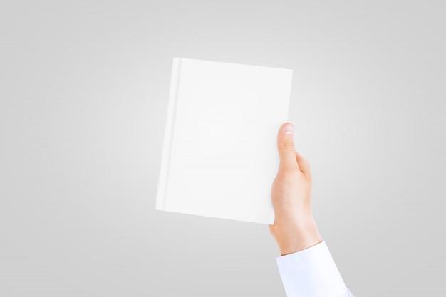Main dans une manche de chemise blanche tenant un livre blanc fermé