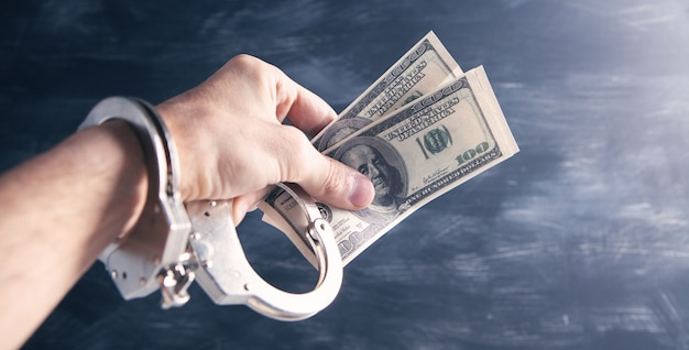 Main dans des menottes tenant de l'argent