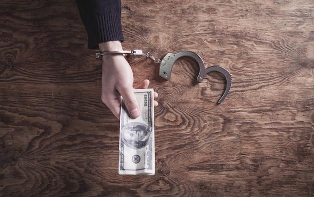 Main dans les menottes tenant des billets en dollars. la corruption