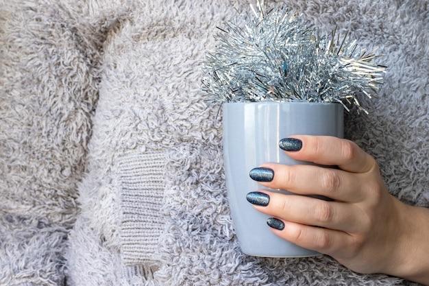 Main dans un pull tricoté moelleux avec des ongles scintillants bleus avec coupe