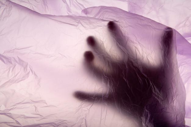 La main dans un sac en plastique. meurtre. fermer. texture mauve