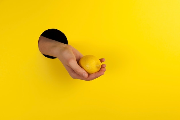 La main dans un trou offre le citron comme source de vitamine c et prévention du rhume et des maladies virales.