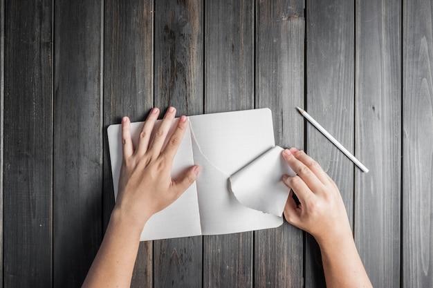 Main déchirant une feuille de bloc-notes