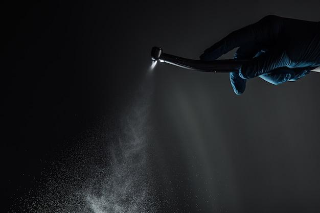 Une main de dentiste avec une perceuse illustre le fonctionnement de la perceuse dentaire avec de l'eau