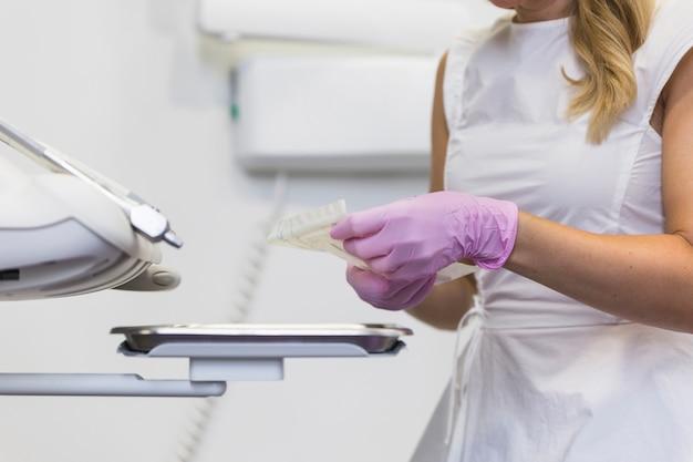 Main de dentiste tenant des outils dentaires en clinique