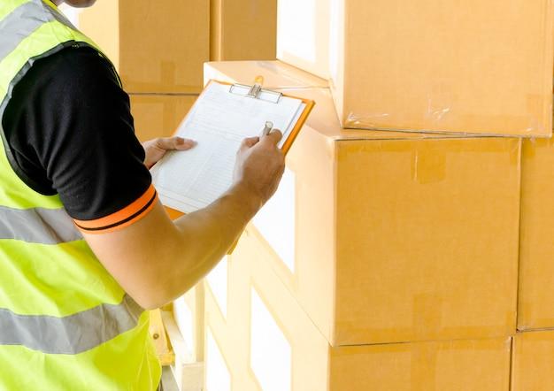 Main dentrepôt tenant presse-papiers inspectant les détails des produits.
