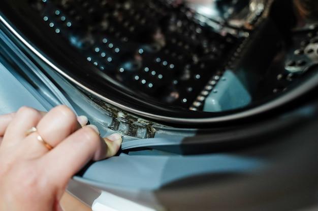 La main dépasse de l'élastique du tambour de la machine à laver avec une couche de saleté en dessous
