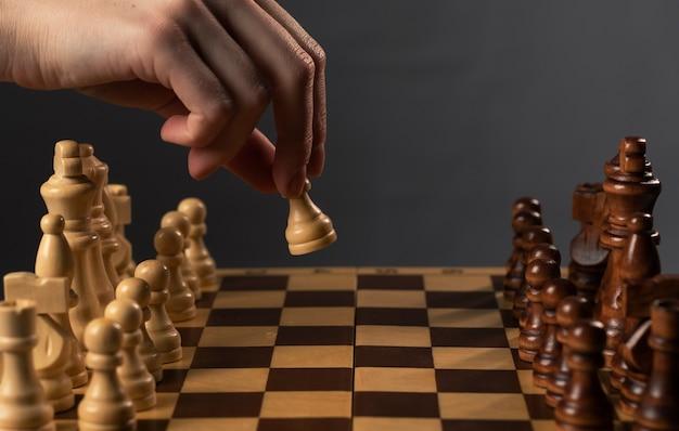 Main déplaçant le pion blanc et faisant le premier pas