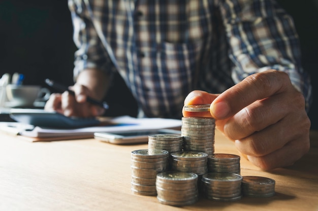 Main déposer une pièce de monnaie avec pile de pièces d'argent de plus en plus pour les entreprises. concept financier et comptable.