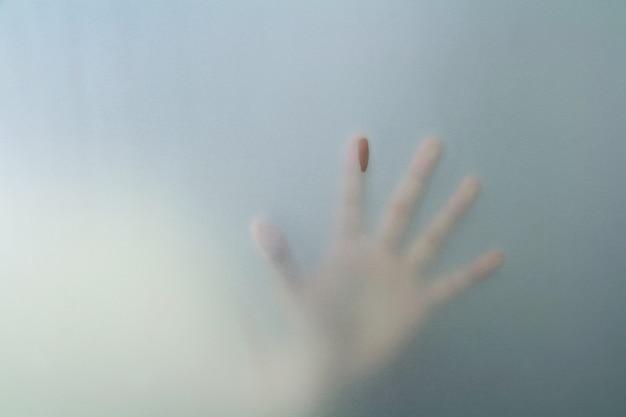 Main derrière verre dépoli