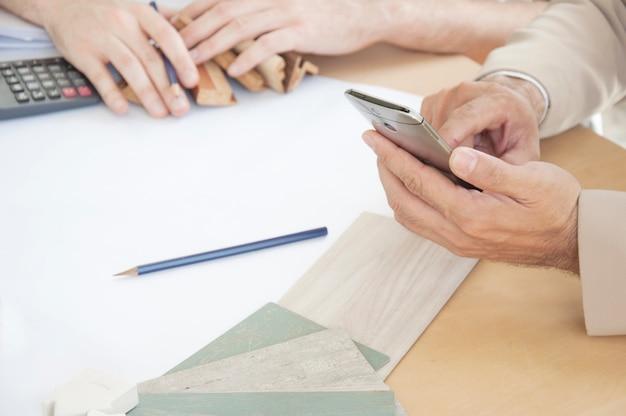 Main designer d'intérieur travaillant avec un téléphone mobile.