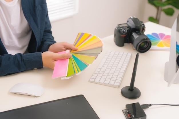 Main d'un designer masculin travaillant à son bureau à l'aide d'un stylet et d'une tablette graphique numérique.