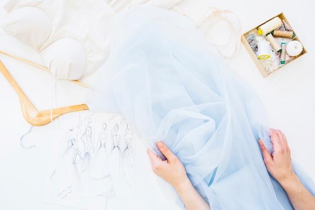 Main de designer avec textile sur établi