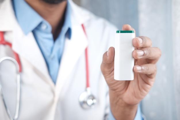 Main de docteur tenant le récipient d'édulcorant artificiel