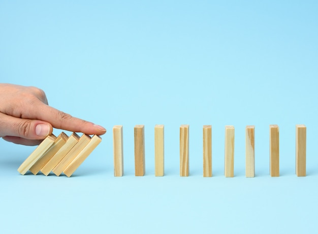 La main avec un doigt arrête la chute des barres de bois sur une surface bleue