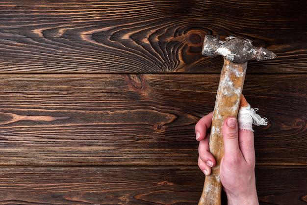 La main avec un doigt blessé tient un marteau sur une table en bois sombre.