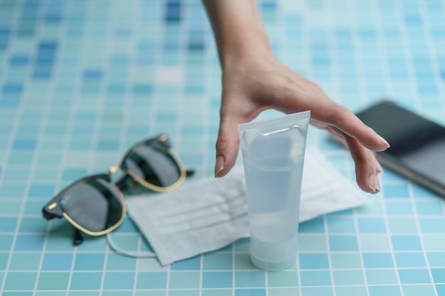 La main avec doit avoir des articles - téléphone intelligent, masque de protection, lunettes et gel corona virus désinfectant, ou protection covid-19.