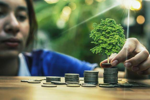 Main donnant une pièce à un arbre poussant à partir de tas en pièce de monnaie. comptabilité financière, concept d'investissement.
