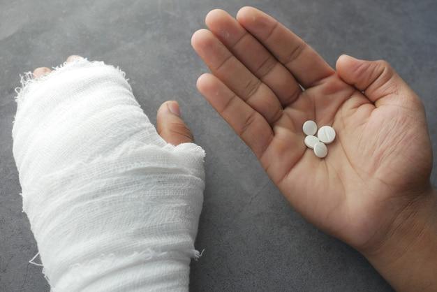 Main douloureuse blessée avec bandage et pilules médicales à portée de main