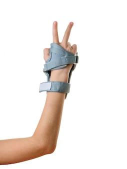 La main droite de l'enfant dans les boucliers protecteurs montre un signe de victoire. accessoires pour la protection contre les chocs.