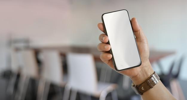 Main droite de l'homme tenant un smartphone à écran blanc