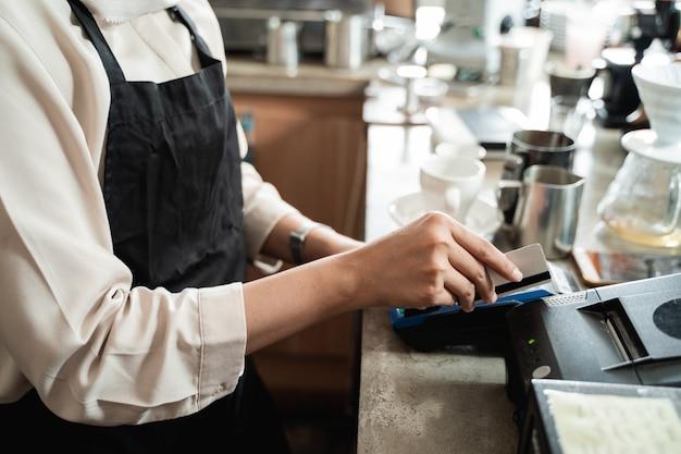 La main du caissier glisse une carte de crédit