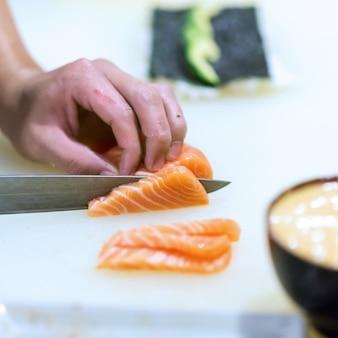 Main du chef faisant du sushi au saumon