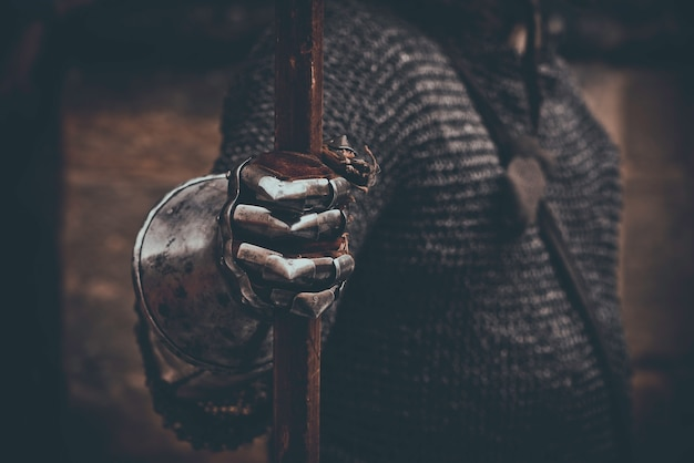 La main du chevalier dans des gants métalliques tenant la lance