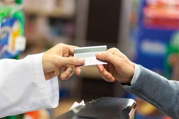 Main du client qui donne sa carte de crédit à la caisse du supermarché à la caisse