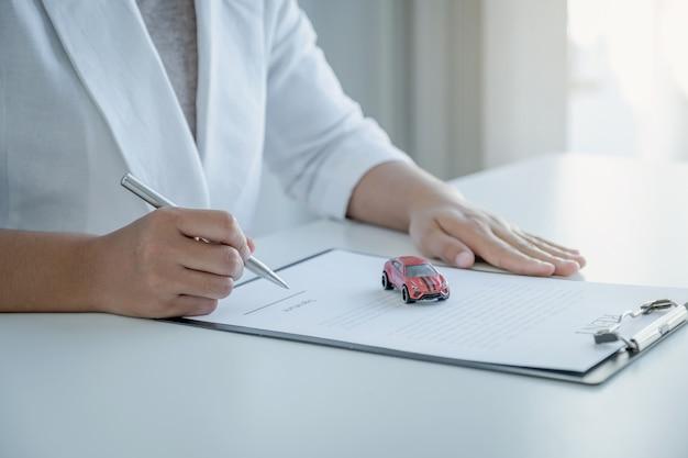 La main du client a signé le contrat d'achat de prêt automobile ou de service de location de véhicule.