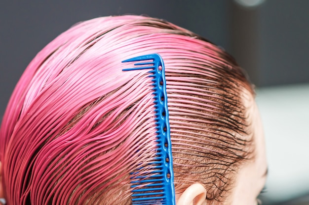 La main du coiffeur peigne les cheveux roses courts et humides d'une femme dans un salon de coiffure en gros plan