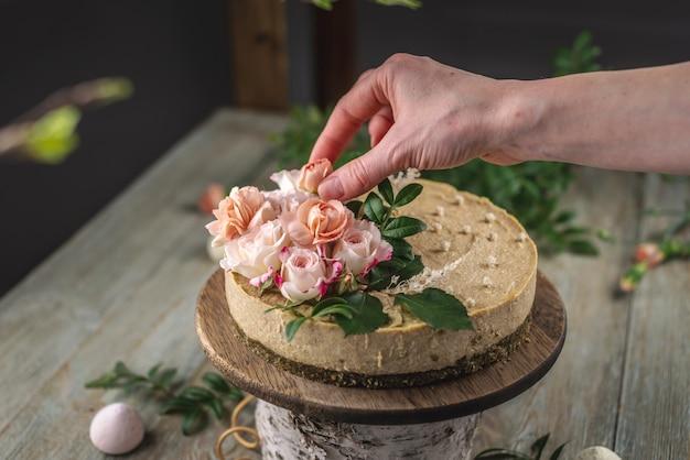 La main du décorateur décorant le délicieux gâteau mousse crue avec des fleurs roses de tendresse
