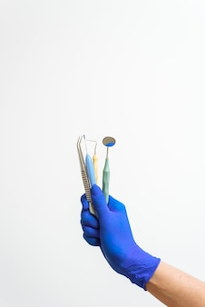 La main du dentiste dans un gant bleu tient des instruments dentaires