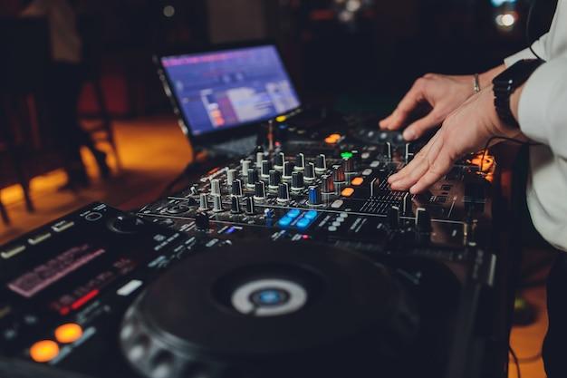 La main du dj sur l'ordinateur portable et la console de mixage contrôlant les paramètres sonores.