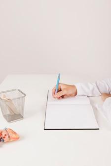 La main du docteur écrit sur son cahier