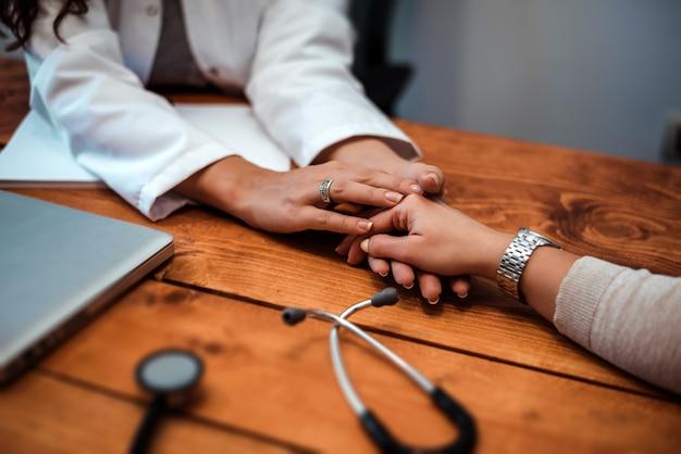 Main du docteur rassurant sa patiente. soins de médecin.