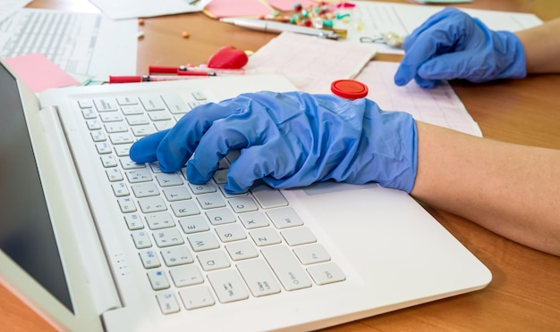 La main du docteur en tapant sur le clavier d'un ordinateur portable