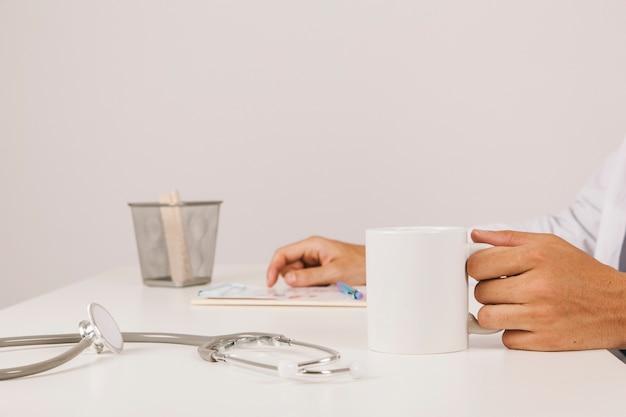 Main du docteur avec une tasse de café au premier plan