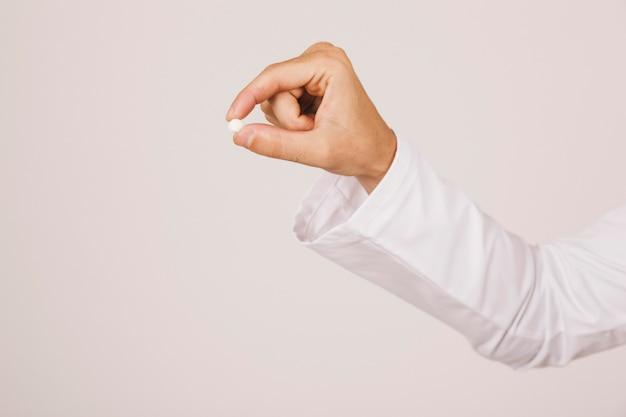 La main du docteur tenant une pilule