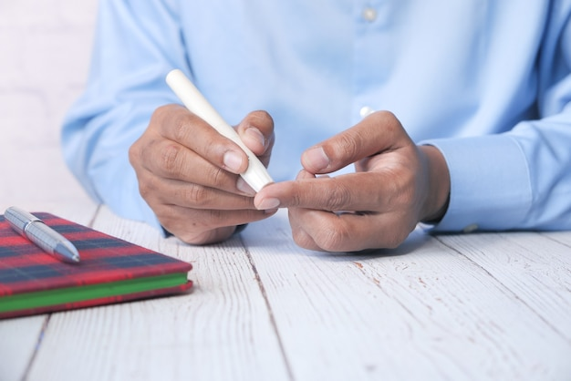La main du jeune homme mesure le niveau de glucose à la maison.