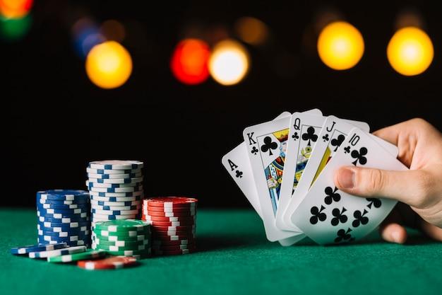 Main du joueur de poker avec club de chasse royale près de jetons sur une surface verte