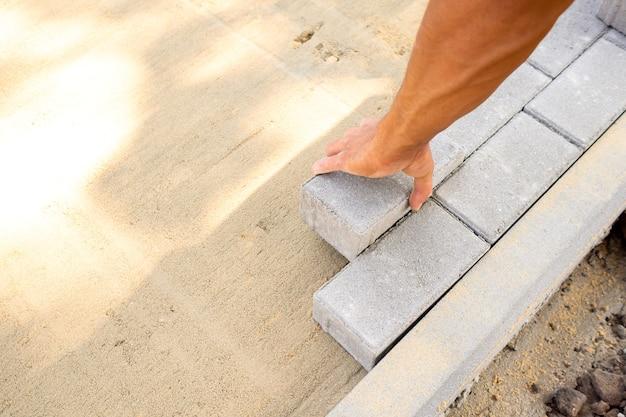 La main du maître met les dalles de pavage dans le mélange de sable préparé. le processus de pose du trottoir, l'amélioration du jardin