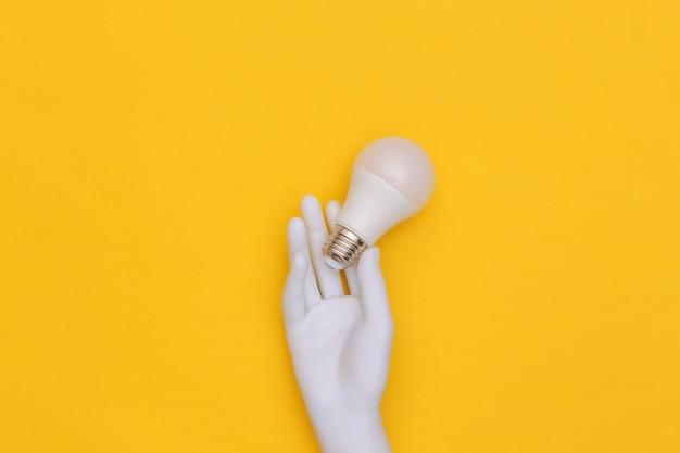 La main du mannequin blanc tient l'ampoule led sur fond jaune. vue de dessus