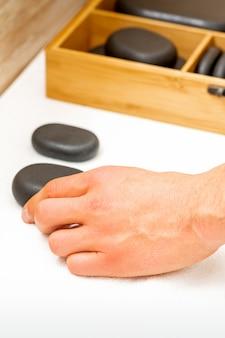 La main du masseur prend des pierres de massage noires de la table dans le salon spa.