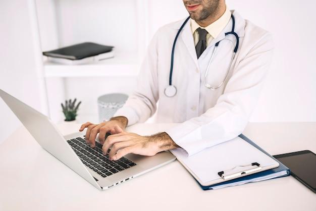 Main du médecin à l'aide d'un ordinateur portable sur le bureau