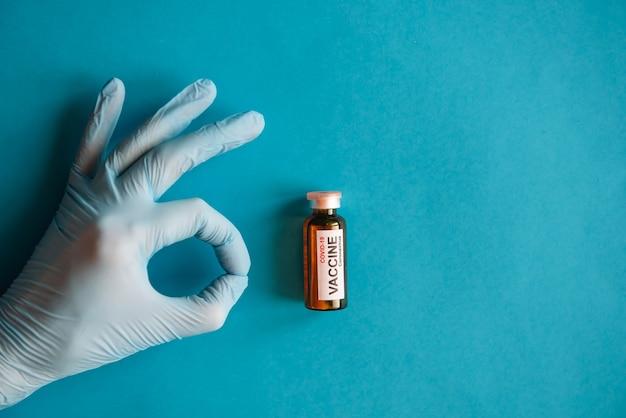 La main du médecin dans un gant en latex médical tenant une ampoule de vaccin contre le coronavirus covid-19 sur fond bleu. geste de la main ok, gros plan