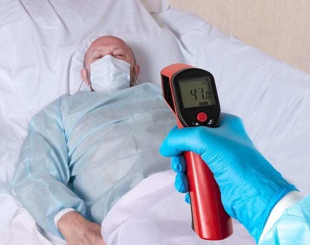 La main du médecin dans un gant tient un thermomètre et mesure la température du patient
