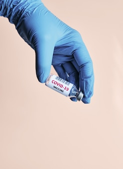 La main du médecin prenant le vaccin covid-19