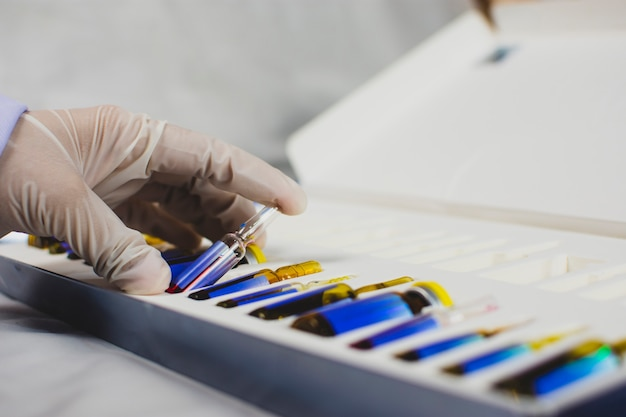La main du médecin prend le flacon d'ampoule de médicament dans le coffret