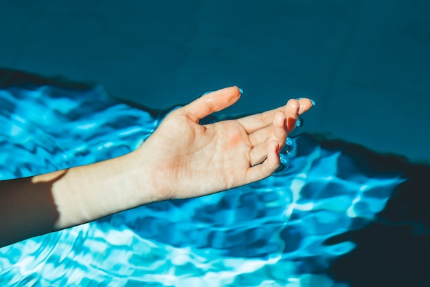 La main du nageur plonge dans une piscine d'eau à l'eau claire bleue transparente, sur laquelle brille la lumière du soleil